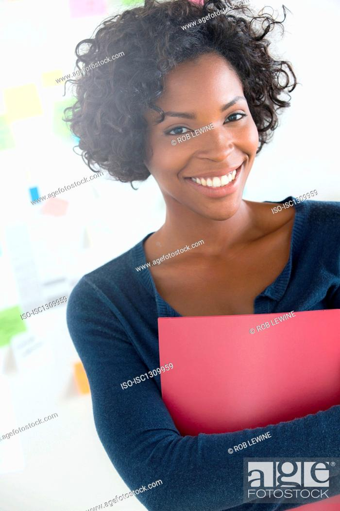 Stock Photo: Portrait of woman holding file in office.