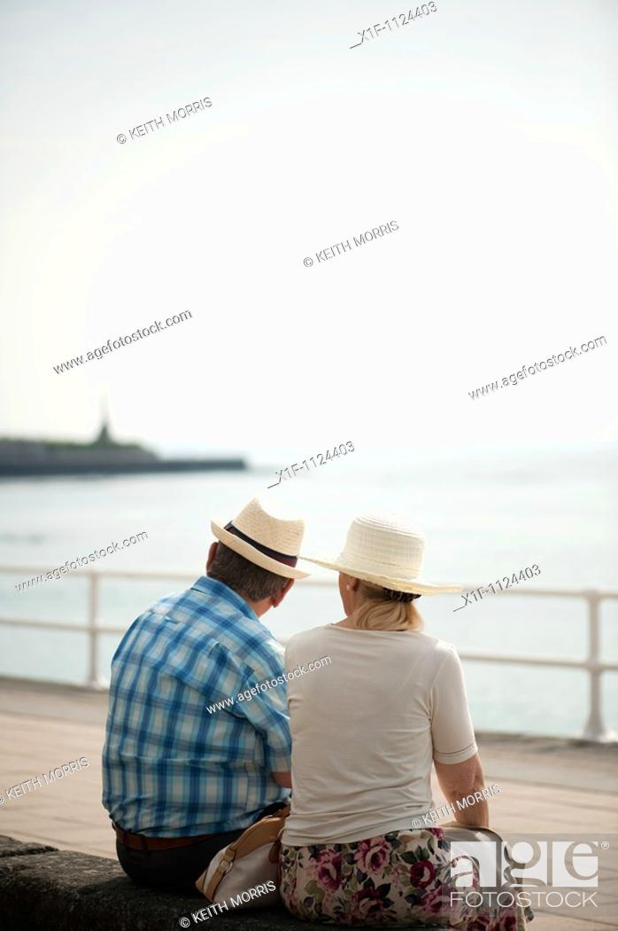 Stock Photo: Rear view of an adult senior couple, man woman, sitting outside wearing hats, Summer afternoon, Aberystwyth Ceredigion wales UK.