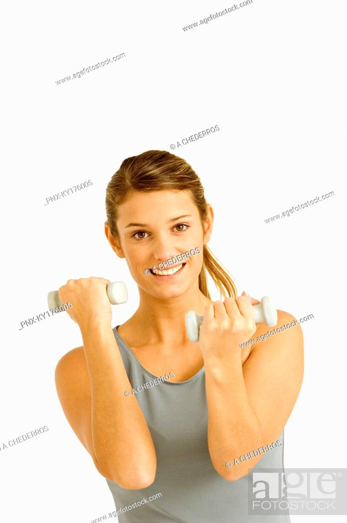 Stock Photo: Portrait of a young woman exercising with dumbbells.
