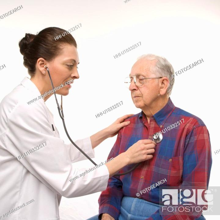 Stock Photo: Mid-adult Caucasian female doctor listening to elderly Caucasian male's heartbeat with stethoscope.