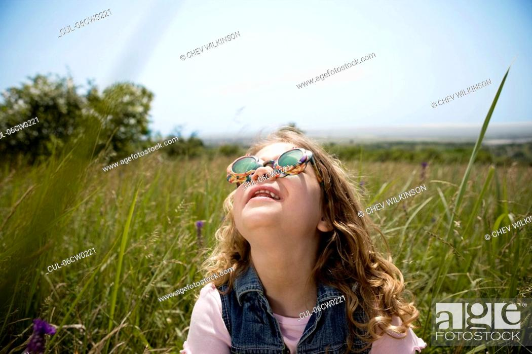 Stock Photo: Girl looking up at sun.