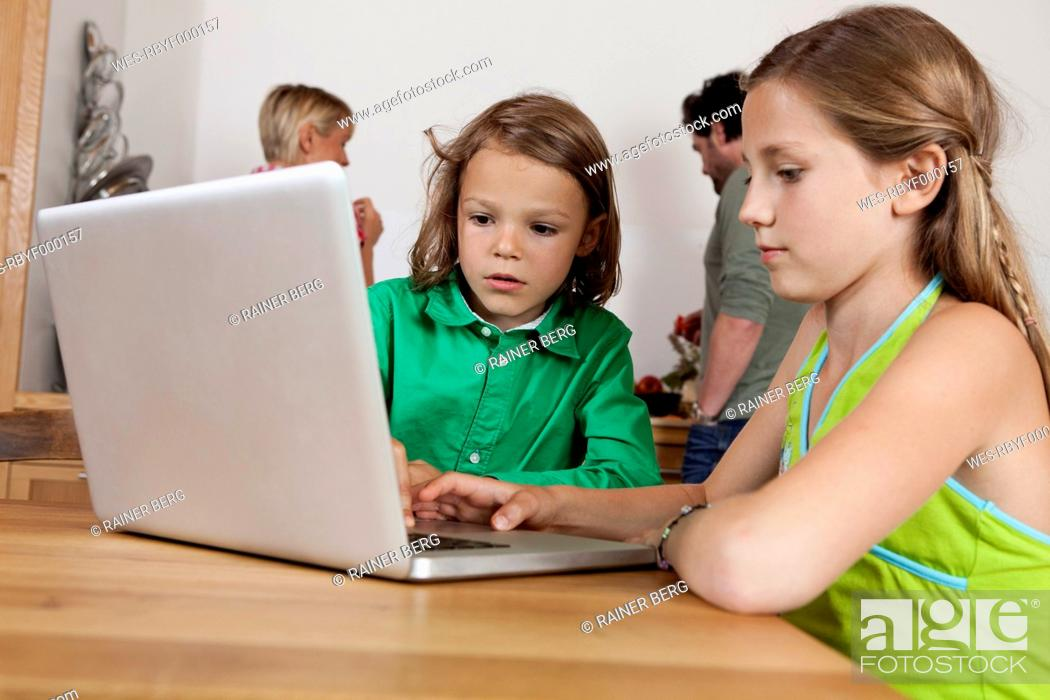 Stock Photo: Germany, Bavaria, Nuremberg, Girl and boy using laptop in kitchen.