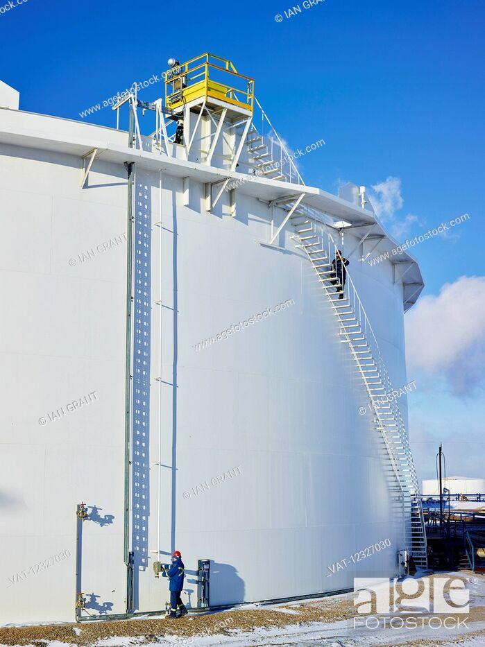 Imagen: Tradesmen working at a large, white storage tank; Edmonton, Alberta, Canada.