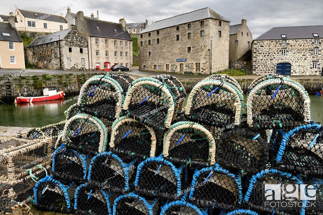 Stock Photo: Lobster traps on stone dock of Old Harbourside Portsoy with stone Portsoy Marble warehouse Aberdeenshire Scotland UK.