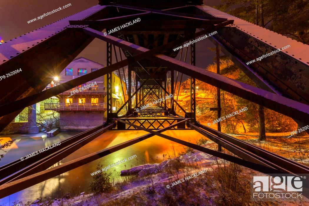 Stock Photo: Underneath a pratt truss rail bridge spanning the Muskoka River. Bracebridge, Muskoka, Ontario, Canada.