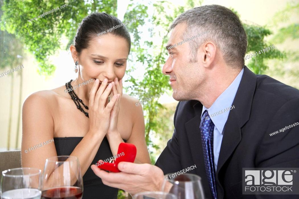 Stock Photo: Man proposing woman with engagement ring.