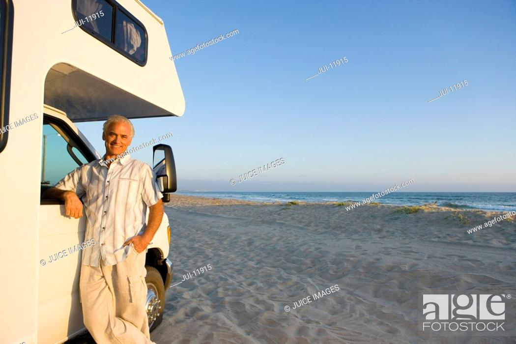 Stock Photo: Mature man by motor home on beach, arm on window, portrait, low angle view.