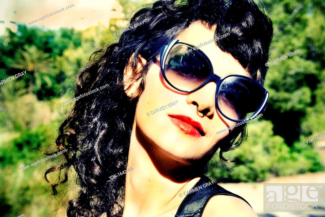 Stock Photo: Portrait of a girl with sunglasses and red lips with green trees behind.