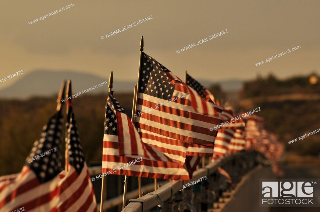 Stock Photo: American flags attached to a bridge over the Santa Cruz River blow in the wind in Green Valley, Arizona, USA.
