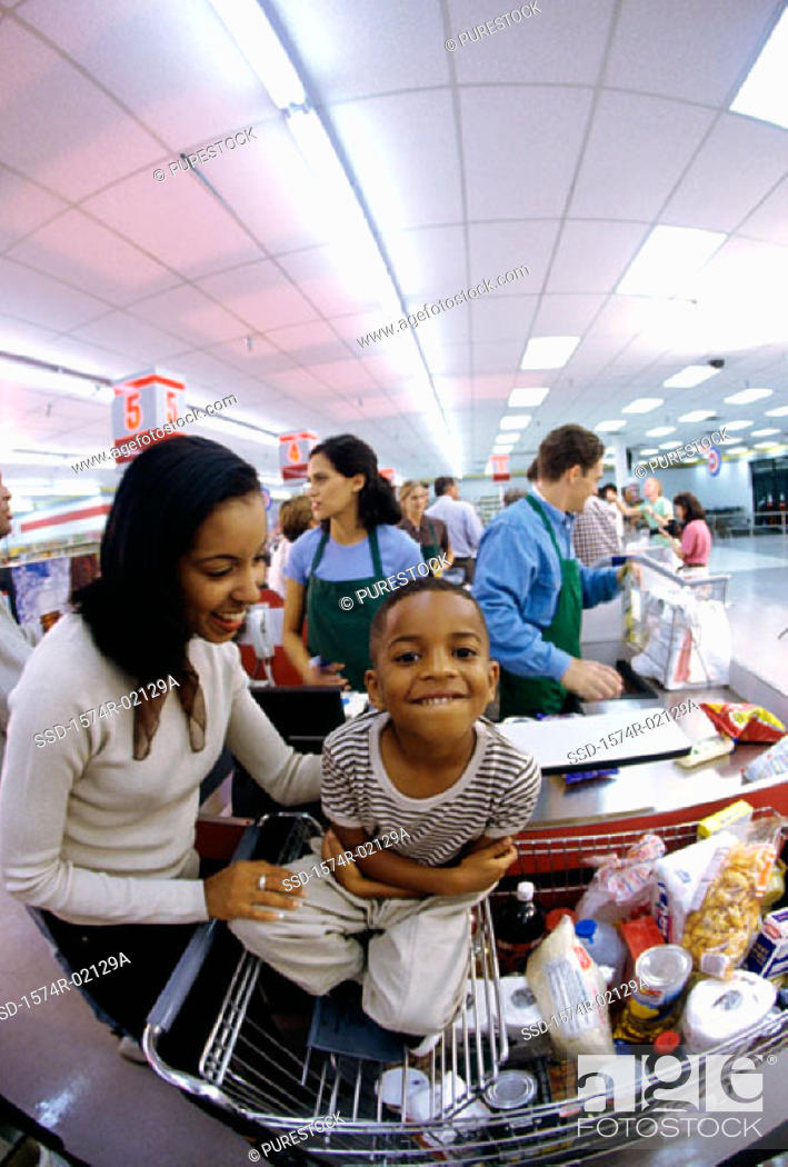 Stock Photo: Mother and her son at a checkout counter in a supermarket.