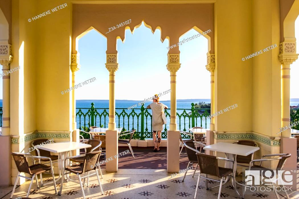 Stock Photo: Girl enjoying the seaviwe from a luxurious hotel in Cienfuegos, Republic of Cuba, Caribbean, Central America.