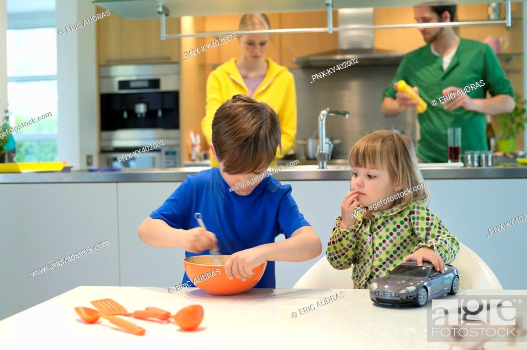 Stock Photo: Little girl with a toy car looking at his brother cooking in the kitchen.