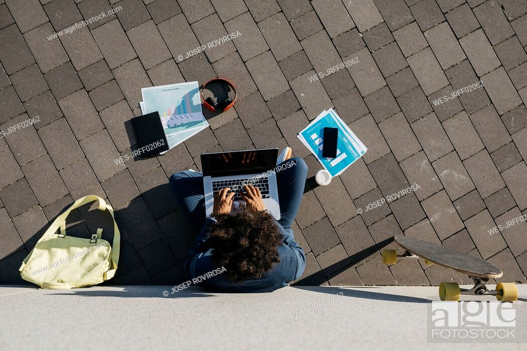 Stock Photo: Young businessman sitting outdoors at a wall working on laptop.