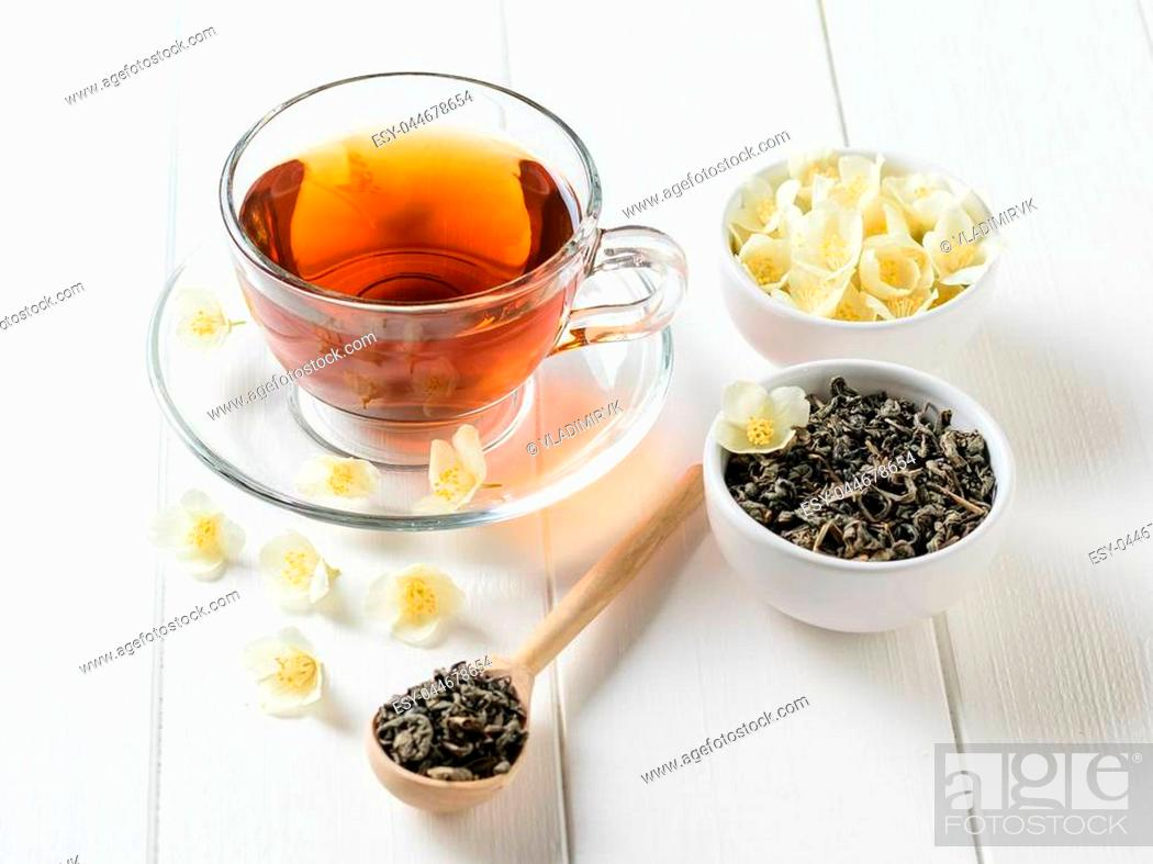 Stock Photo: Freshly prepared tea with Jasmine flowers on a white wooden table. The view from the top. Spring tea composition.