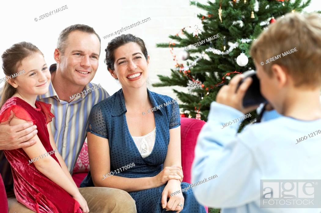 Stock Photo: Boy taking photo of sitter mother and father by christmas tree.