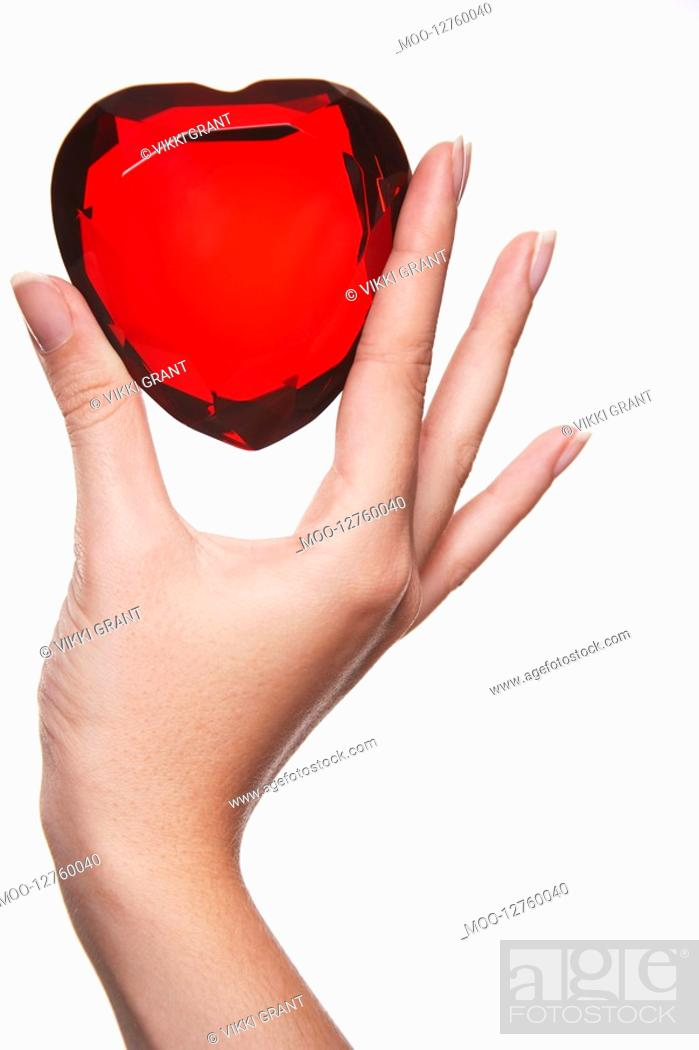 Stock Photo: Woman holding up heart-shaped jewel between finger and thumb close-up of hand.