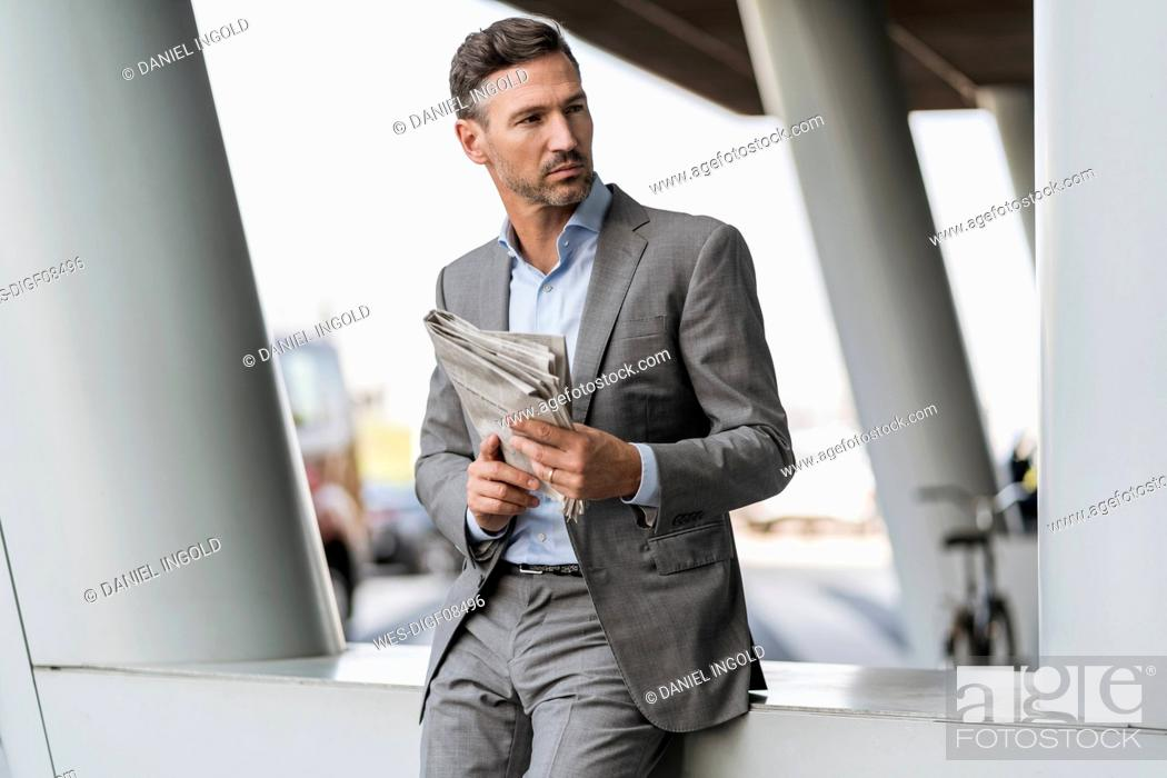 Stock Photo: Portrait of businessman with newspaper outdoors.