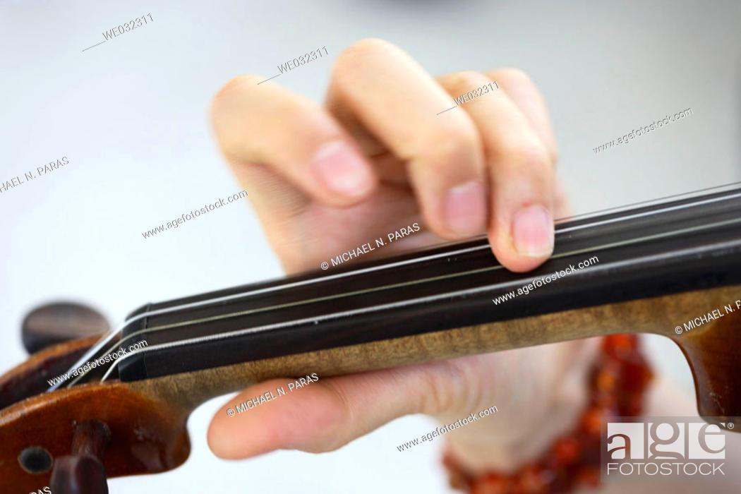 Imagen: Woman's fingers on neck of violin.