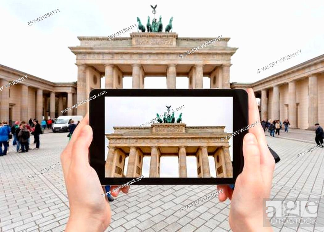 Imagen: travel concept - tourist takes picture of Brandenburg gate in Belin in cloudy autumn day on Pariser Platz on tablet pc.