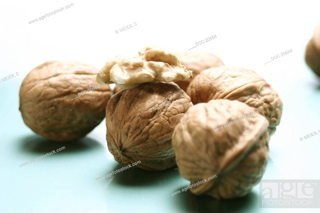 Imagen: several whole walnuts with a piece of inner nut on white ground.