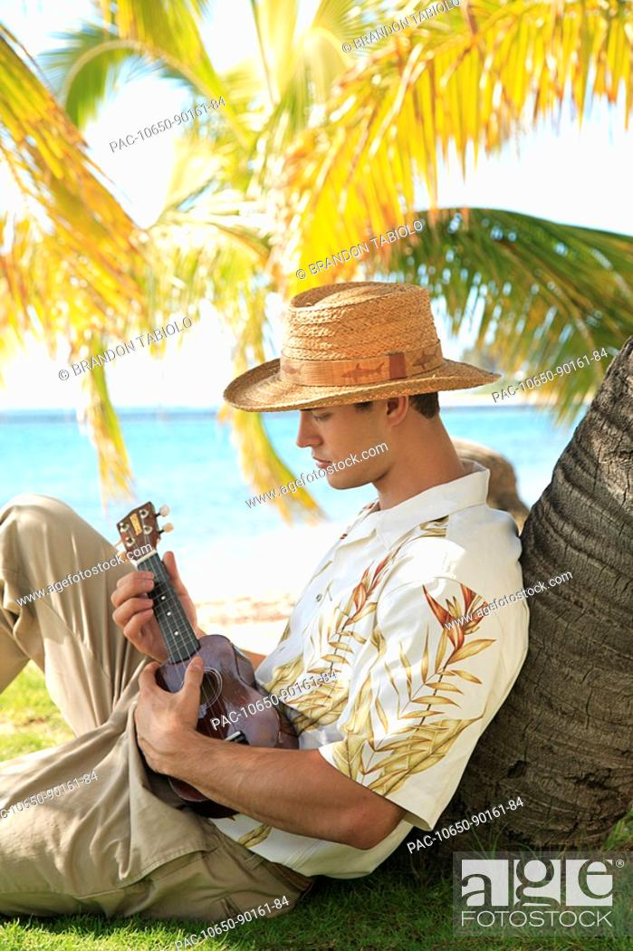 Imagen: Hawaii, Oahu, Young male with vintage aloha shirt and straw hat relaxing holding a ukulele.