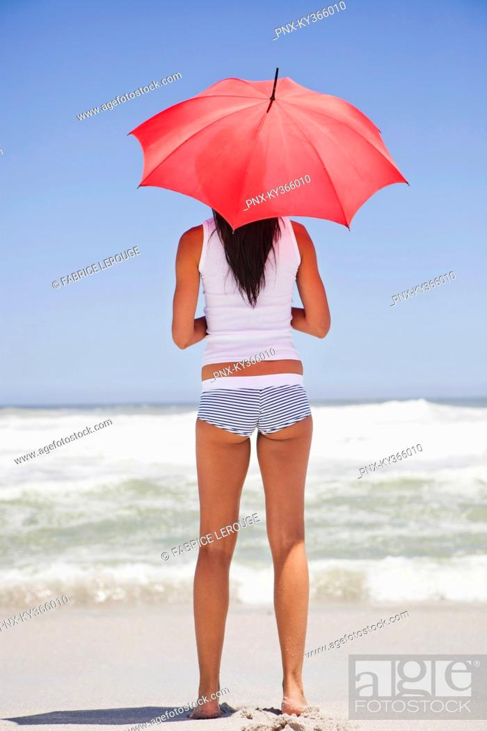 Stock Photo: Woman standing on the beach with an umbrella and looking at sea view.