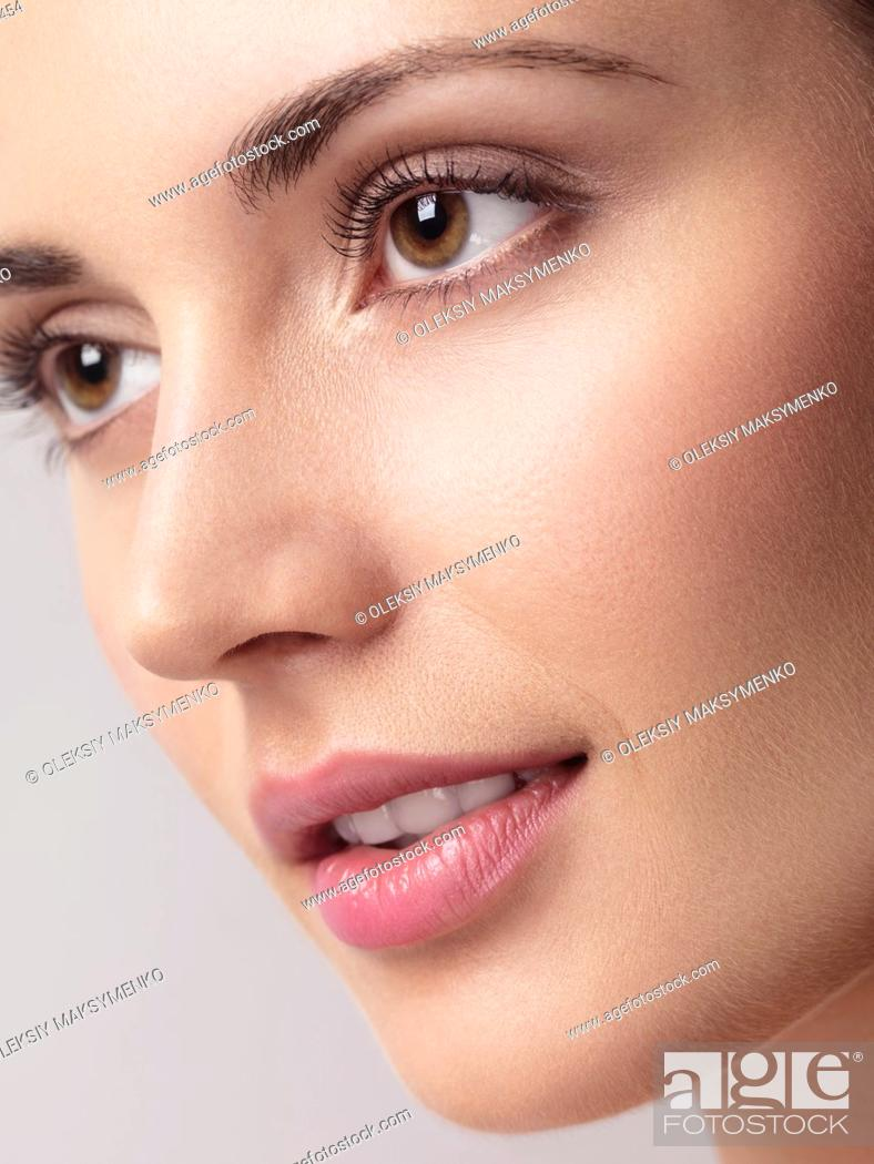 Stock Photo: Closeup of a young beautiful woman face with clean natural look and smooth skin.