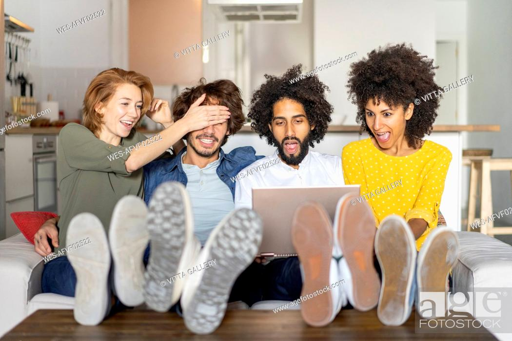 Stock Photo: Friends sitting on couch, watching laptop.