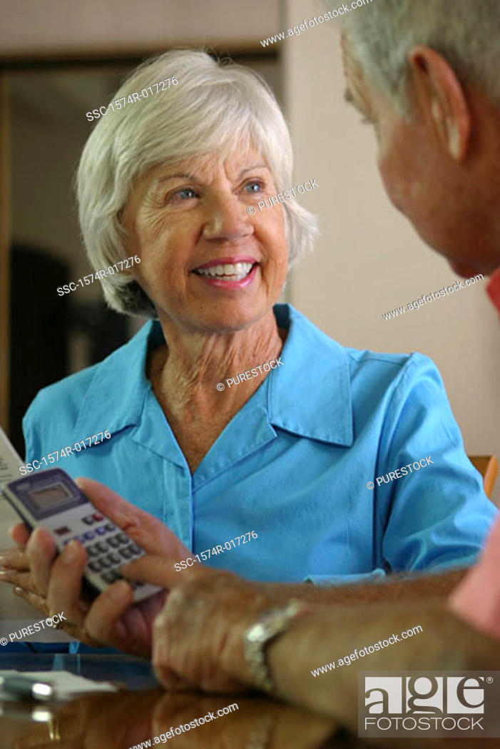 Stock Photo: Senior man using a calculator with a senior woman sitting beside him.