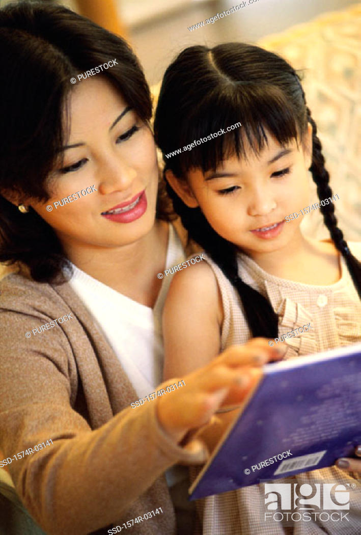 Stock Photo: Mother reading a storybook with her daughter.