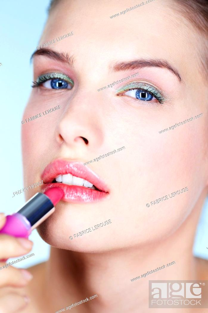 Stock Photo: Portrait of young woman applying lipstick.