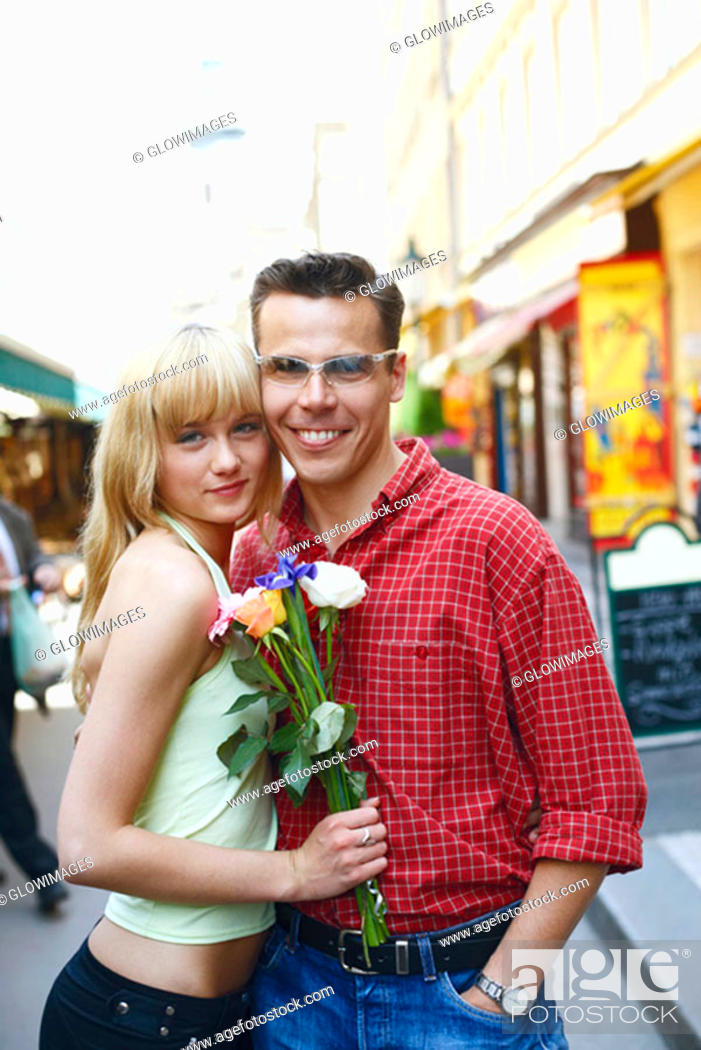 Stock Photo: Portrait of a young woman and a mid adult man standing on the street.