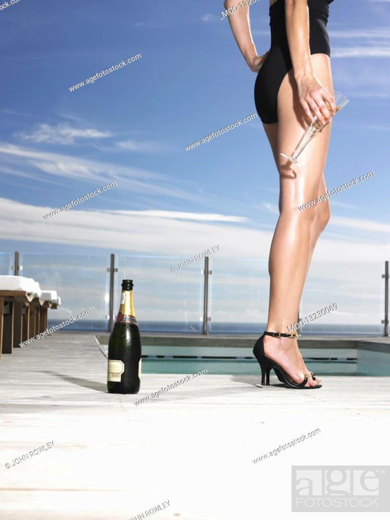 Stock Photo: Woman in bathing suit standing with champagne at outdoor pool low section.