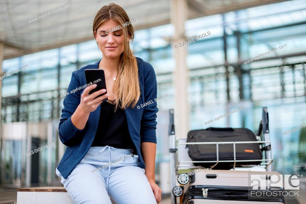 Stock Photo: Smiling young businesswoman sitting outdoors with cell phone and suitcase.