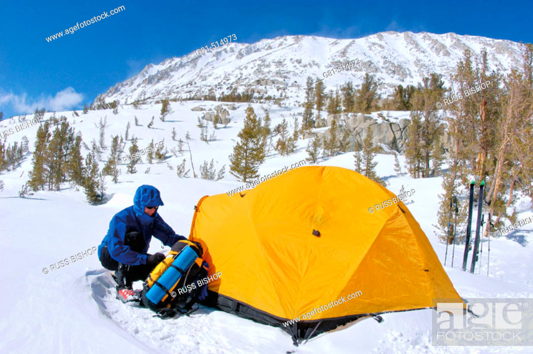 Stock Photo: Skier and Yellow dome tent in a backcountry ski camp in Little Lakes Valley, Inyo National Forest, Sierra Nevada Mountains, California.