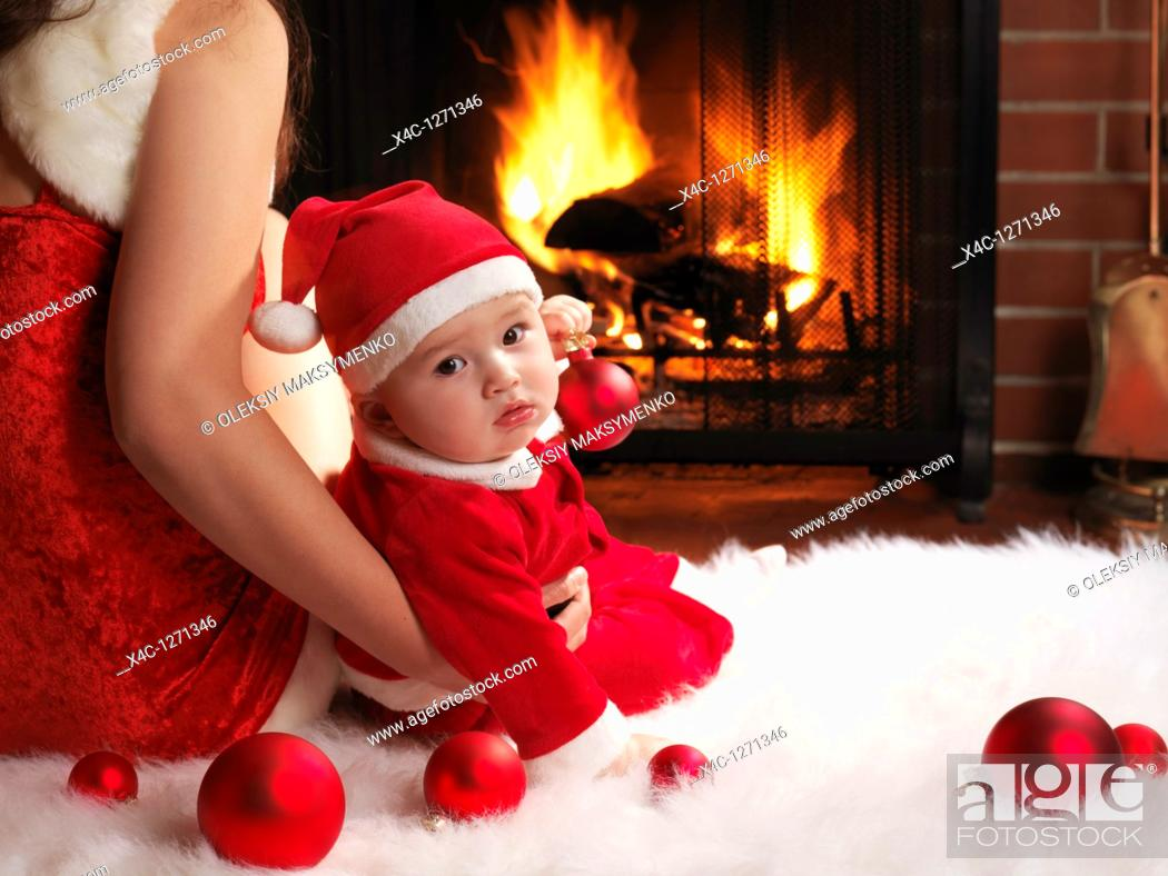 Stock Photo: Mother and a little baby boy sitting in front of a fireplace in Christmas costumes.
