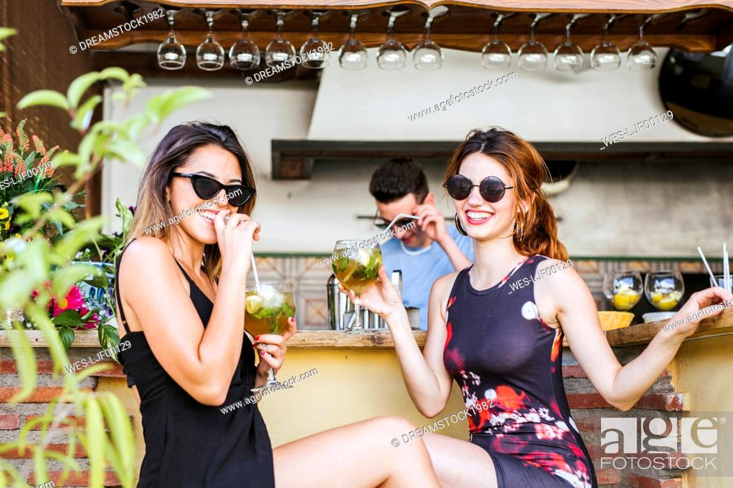 Stock Photo: Two women having a drink at a bar.