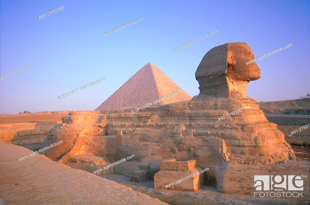 Stock Photo: EGYPT.CAIRO.GIZEH.THE SPHINX AND PYRAMIDS AT BACK AT SUNRISE.