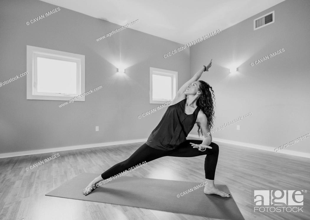 Imagen: black and white image of middle age woman doing yoga in a studio.