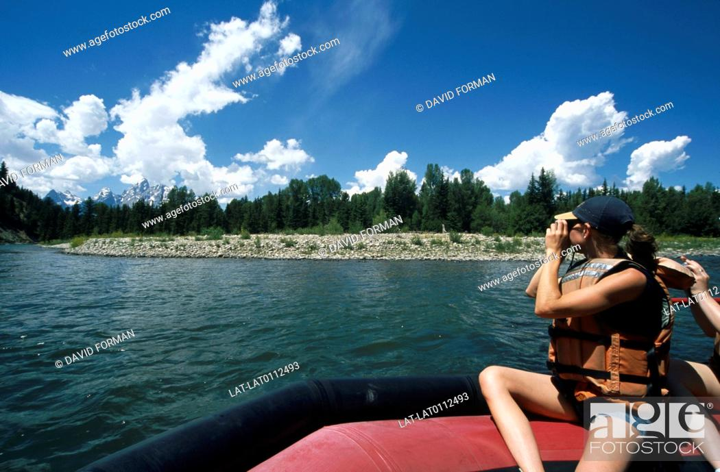 Stock Photo: The Snake River running through the national park. A woman in an inflatible boat taking a photograph of the mountains.