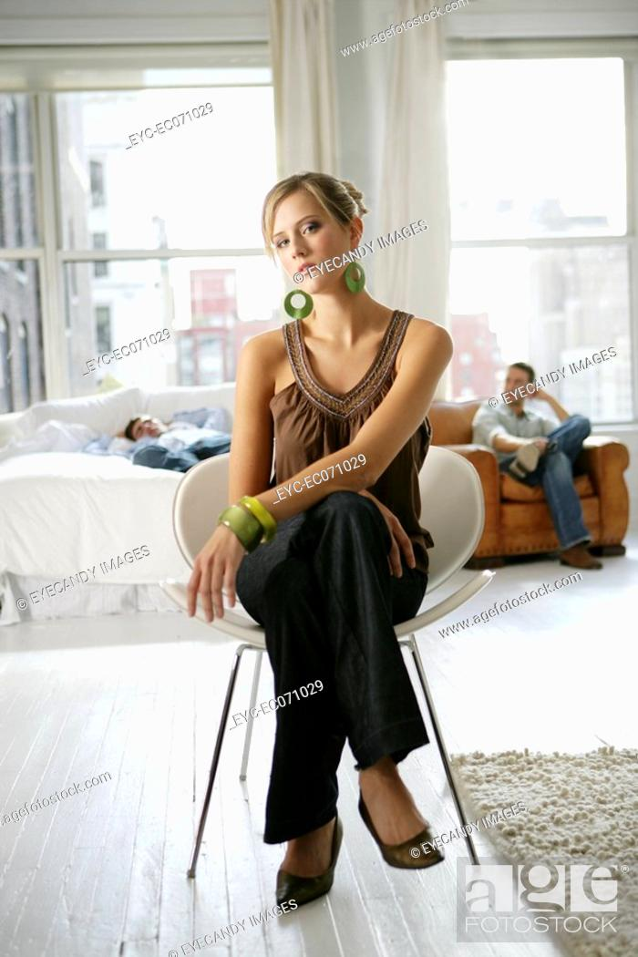 Stock Photo: Young stylish woman sitting chair with men behind.