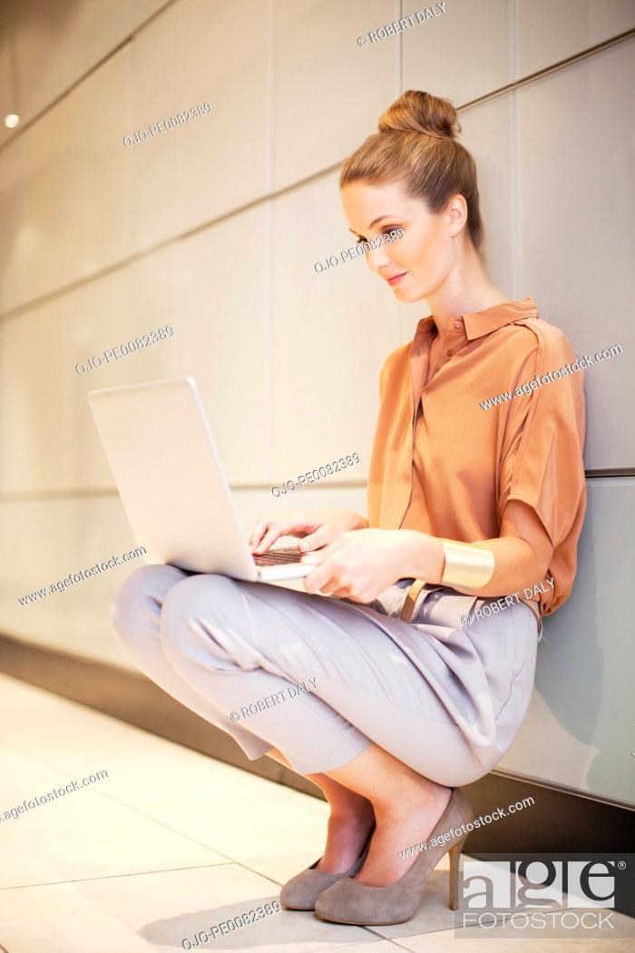 Stock Photo: Smiling businesswoman using laptop in corridor.