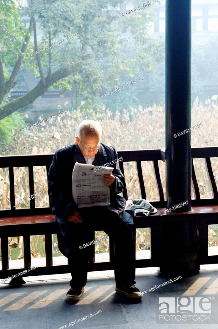 Stock Photo: Elderly Chinese man reading newspaper in temple courtyard garden of the Wu Hou Shrine in city of Chengdu, Sichuan Province China.