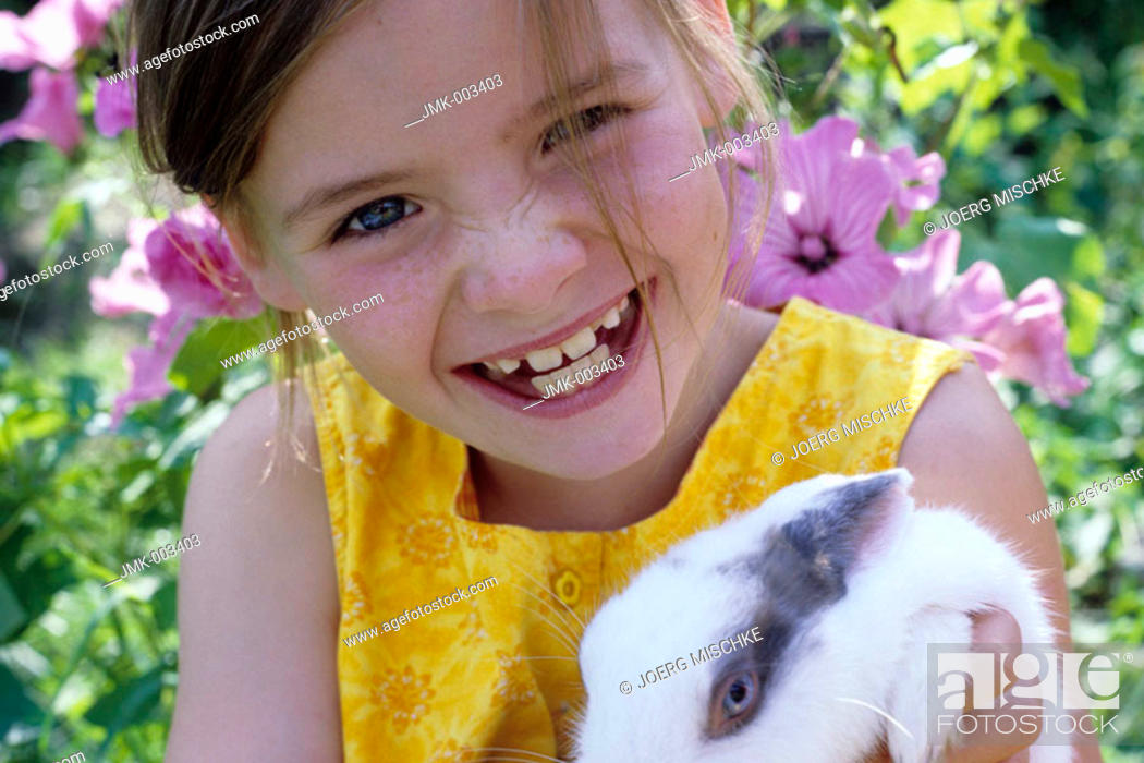 Imagen: Portrait of a girl, 5-10 years old, in the garden in summer, holding a rabbit, bunny in it's arms.