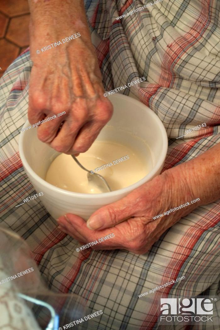 Stock Photo: An old woman stirring homemade icing in a bowl on her lap.