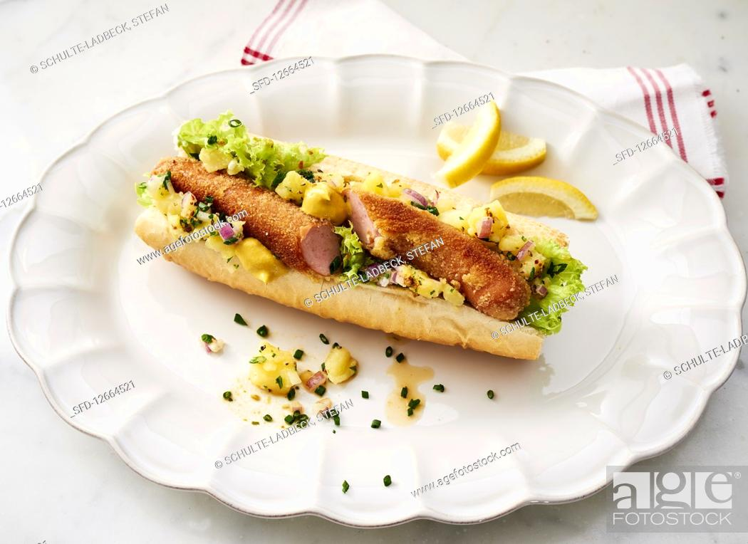 Stock Photo: Viennese-style hot dog with potato salad and lemon wedges.