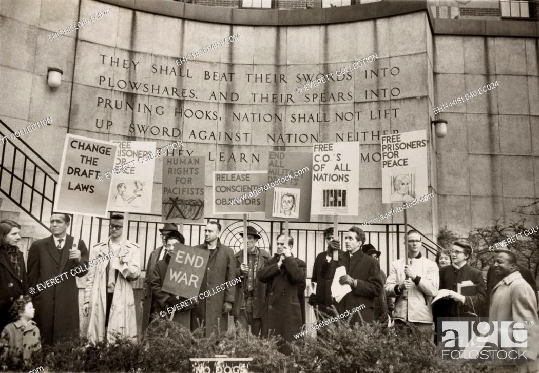 Stock Photo: Conscientious objectors from the War Resisters League picketing near the United Nations in New York City. In front of biblical quotation inscribed behind them.