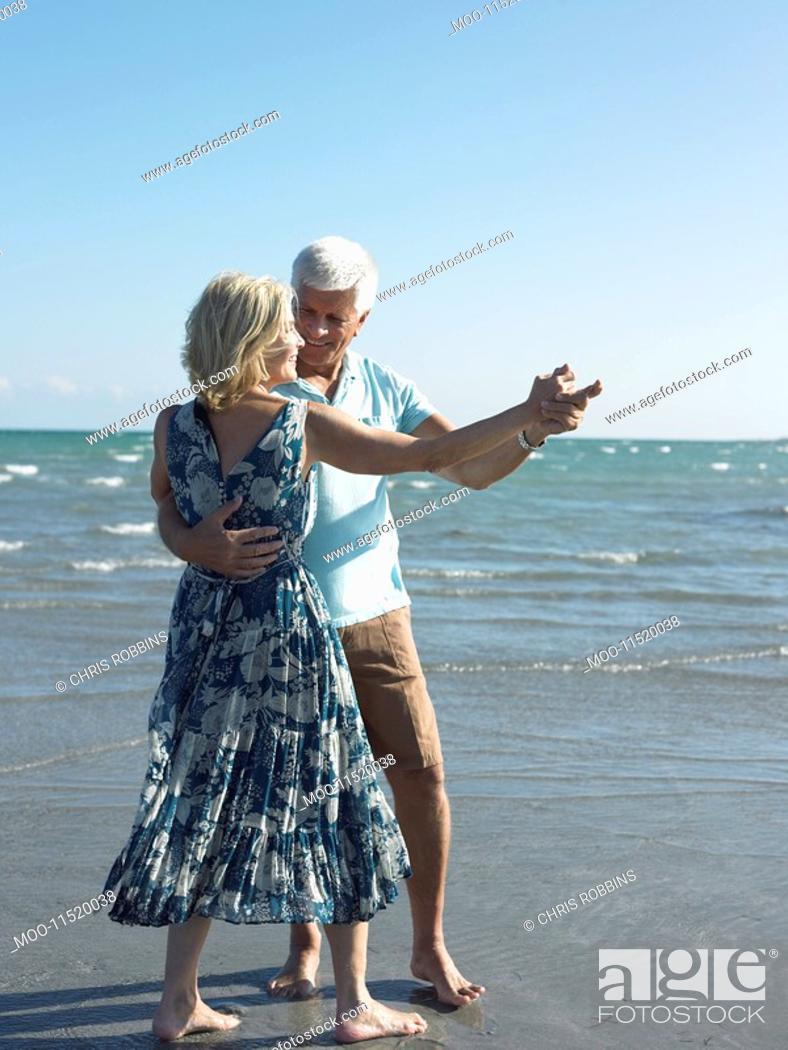 Stock Photo: Senior couple dancing on beach.