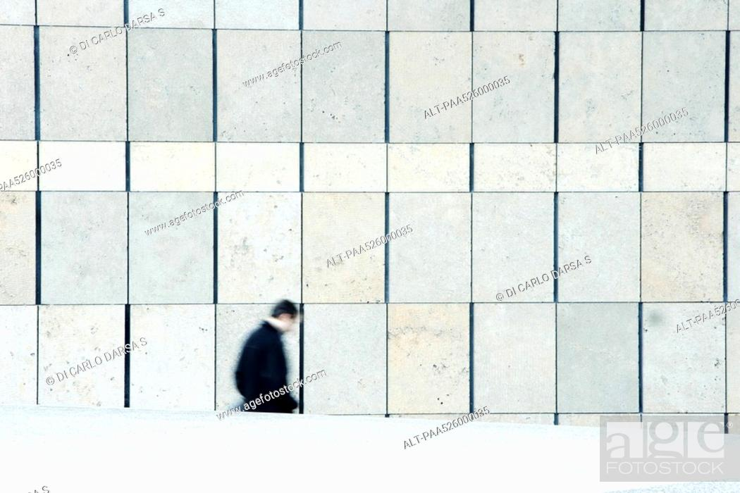 Stock Photo: Businessman descending stairs leading down from sidewalk.