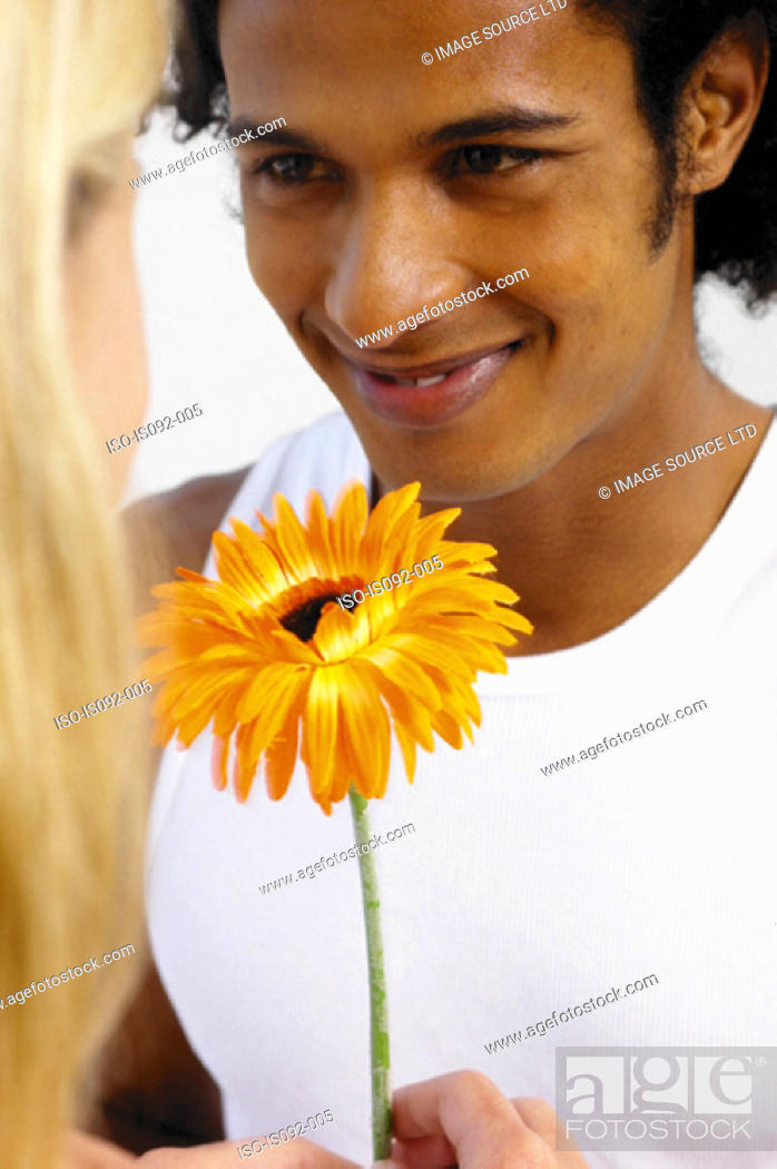 Stock Photo: Man giving flower to woman.